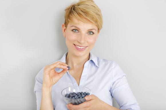 Femme blonde mangeant des myrtilles