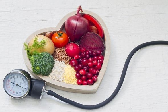 Moniteur de pression artérielle et légumes dans un bol en forme de coeur