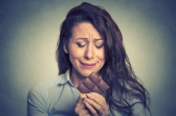 Brunette qui pleure sur une barre de chocolat
