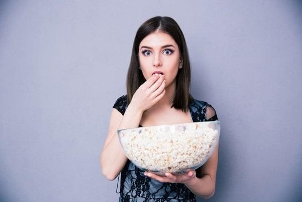 Brunette mangeant du pop-corn dans un grand bol