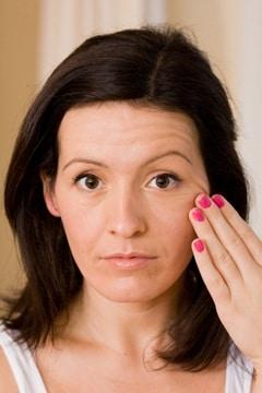 Brunette touchant la peau de son visage