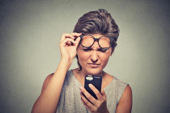 Brunette avec des lunettes ayant des difficultés à lire son téléphone portable