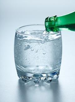 L'eau gazeuse étant versée dans un verre