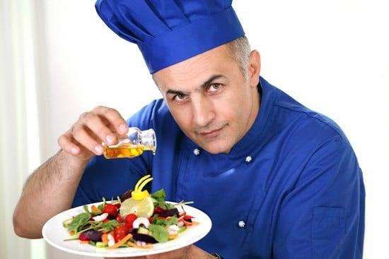 Chef verser de l'huile d'olive sur une salade, plus petite