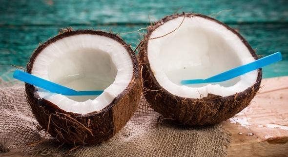 Noix de coco coupée en deux avec des pailles bleues