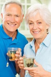 Homme âgé et femme tenant des tasses de thé