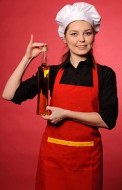 Chef féminin tenant une bouteille d'huile d'olive