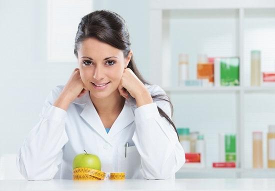 Nutritionniste féminine avec une pomme au bureau