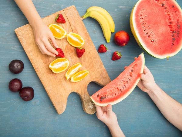 Fruits sur une planche à découper et les mains à la recherche de fruits