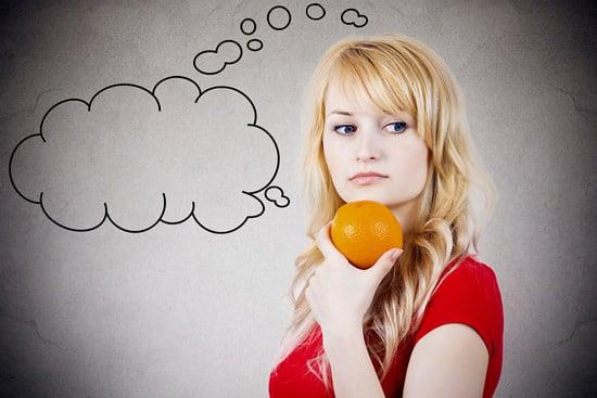 Fille tenant une orange et de la pensée
