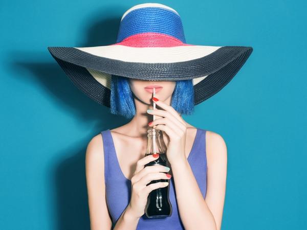Fille avec un chapeau et une perruque bleue buvant du soda