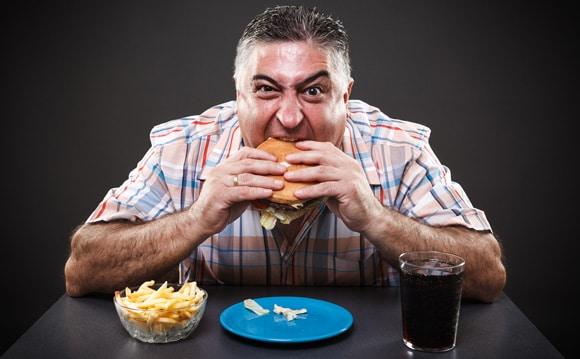 Homme gourmand et en surpoids, manger de la malbouffe