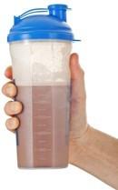 Main tenant une boisson protéinée