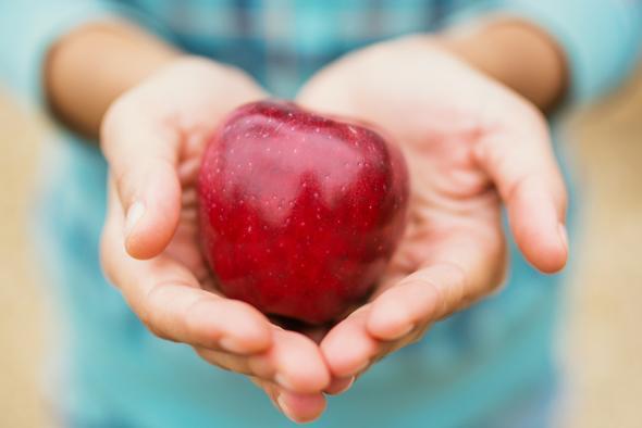 Mains tenant une pomme