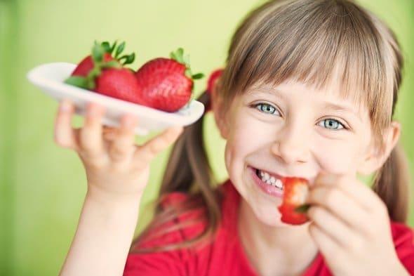 Petite fille mangeant des fraises