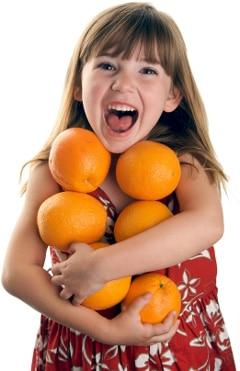 Petite fille tenant des oranges