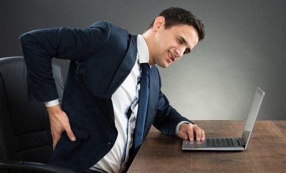Homme en costume avec des maux de dos de s'asseoir
