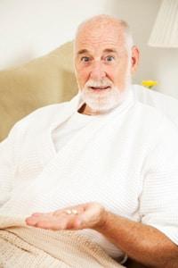 Vieil homme prenant des pilules