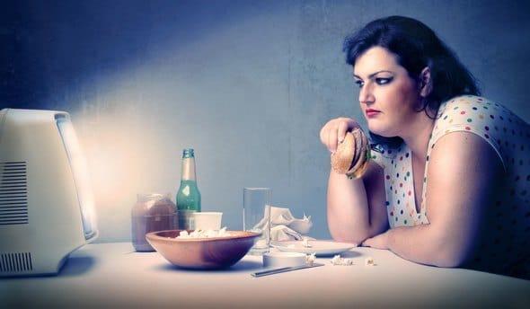 Femme en surpoids mangeant devant la télévision