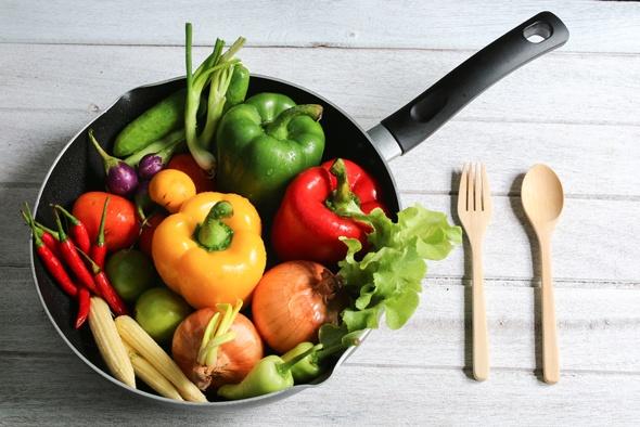 Poivrons, oignons et autres légumes crus dans une poêle