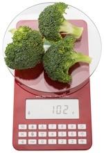 Ensemble rouge de balances pesant le brocoli