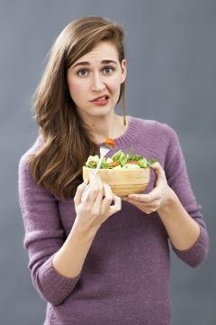 Sceptique, jeune femme, manger, salade