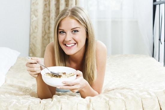 Sourire blonde manger des céréales au lit