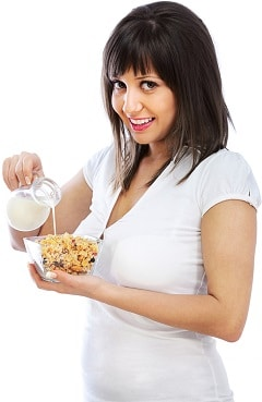 Brunette souriante, verser le lait sur les céréales