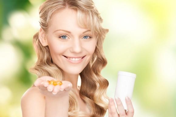 Femme souriante tenant des capsules oméga-3