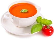 Tomate, soupe de tomates et feuilles de basilic