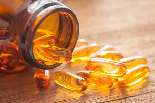 Bouteille de vitamine D sur le côté avec certaines capsules versées