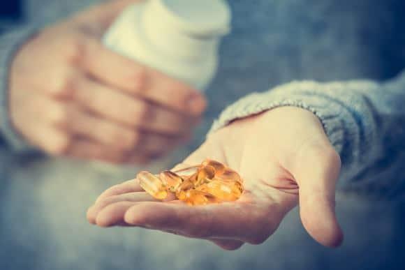 Capsules de vitamine D dans la main de l'homme