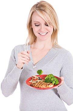 Femme mangeant du saumon et du brocoli