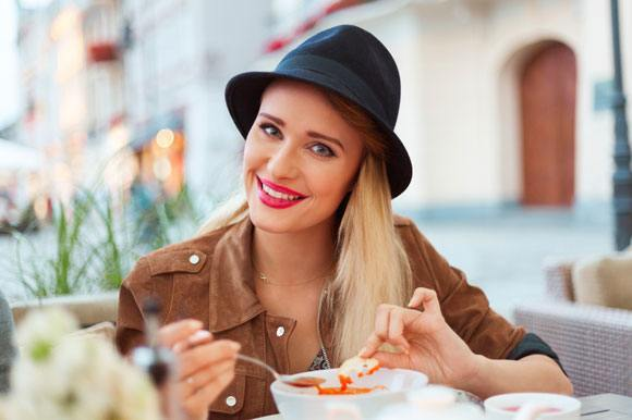 Femme mangeant de la soupe aux tomates au restaurant en plein air