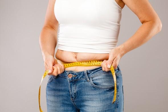 Femme prendre du poids et mesurer le ventre