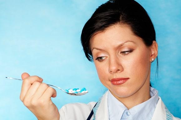 Femme tenant une cuillère pleine de pilules