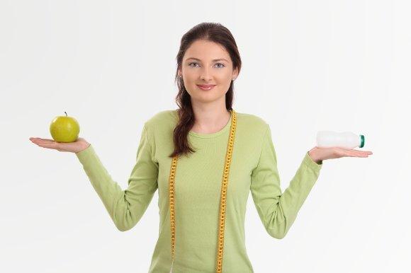 Femme tenant des probiotiques et Apple