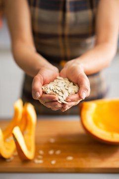 Femme tenant des graines de citrouille dans ses mains