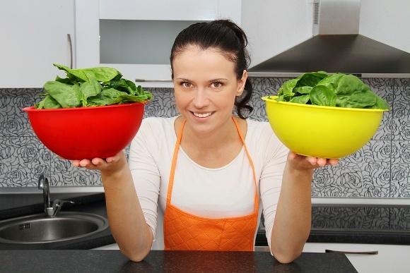 Femme tenant deux bols d'épinards verts