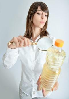 Femme, inspection, bouteille huile, à, loupe