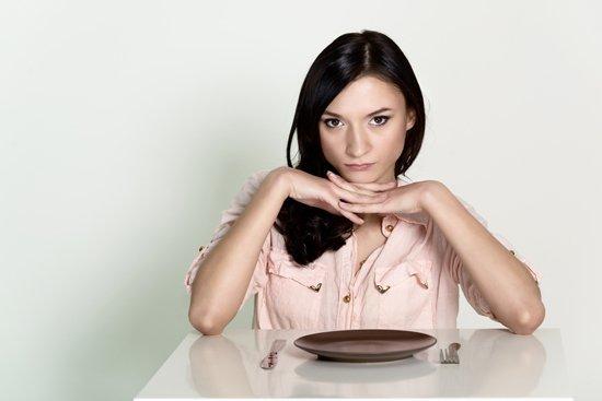 Femme assise avec une assiette vide