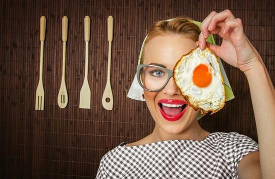 Femme souriante et tenant un œuf au plat