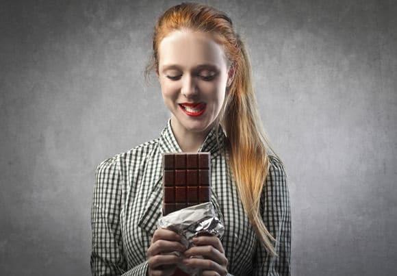 Femme aux cheveux rouges tenant une barre de chocolat