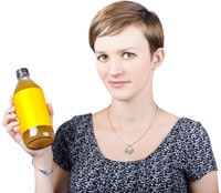 Femme aux cheveux courts tenant une bouteille de vinaigre de cidre de pomme