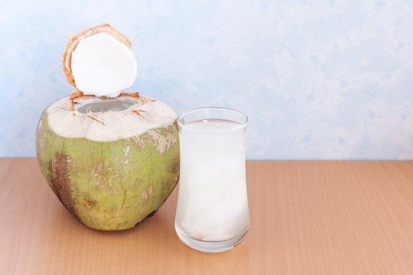 Jeune noix de coco et eau de coco dans un verre