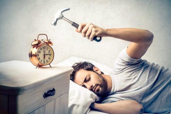 Jeune homme voulant frapper le réveil