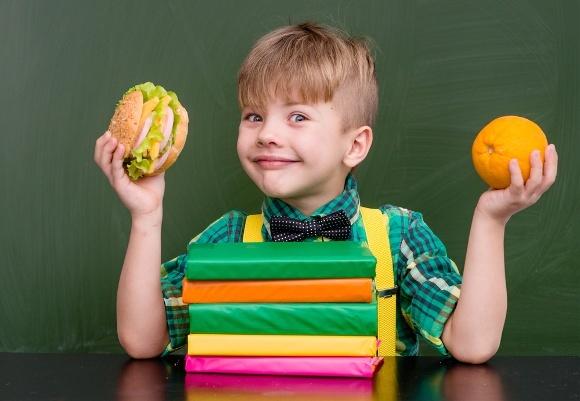 Jeune écolier tenant de la nourriture