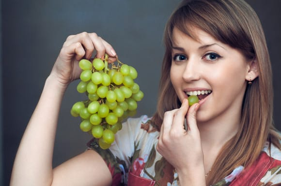 Jeune femme, manger, raisins verts