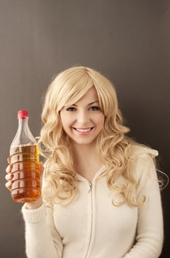 Jeune femme tenant une bouteille de vinaigre de cidre de pomme