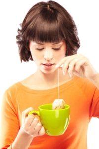 Jeune femme faisant une tasse de thé vert